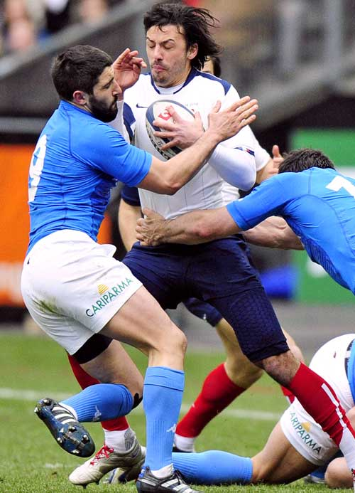 France's Clement Poitrenaud is wrapped up by the Italy defence