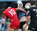 The Sharks' Steven Sykes is tackled by the Reds' Quade Cooper