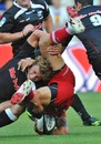 The Sharks' Patrick Lambie tackles the Reds' Quade Cooper