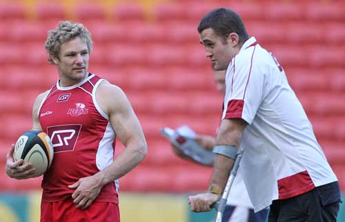 The Reds' Peter Hynes talkes to injured team-mate James Horwill