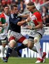 Biarritz's Imanol Harinordoquy fends off Munster's Alan Quinlan