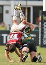 Northampton's Dylan Hartlet tackles Saracens' Schalk Brits