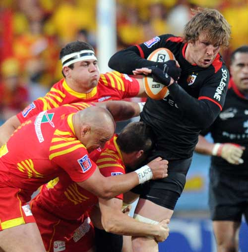 Toulouse No.8 Shaun Sowerby is tackled by the Perpignan defence