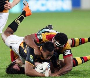 Wellington star Julian Savea is tackled by Waikato's Dominiko Waqanibburotu