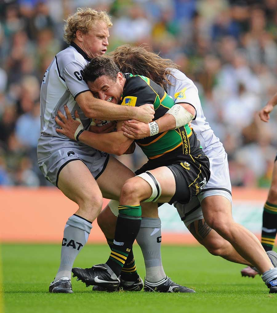 Northampton's Phil Dowson is wrapped up by the Leicester defence