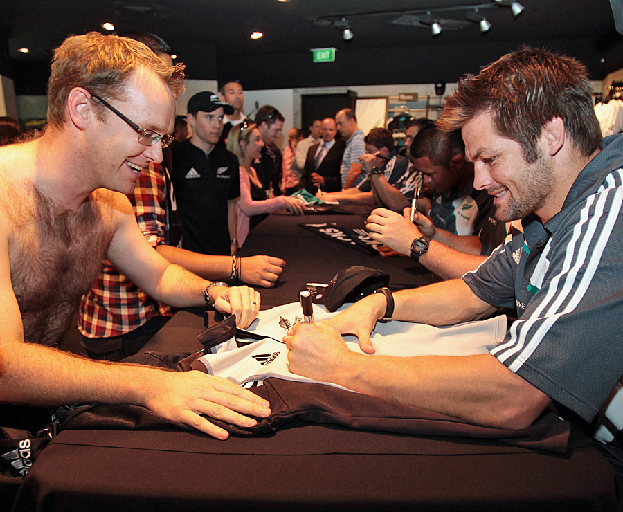 Richie McCaw signs a shirt for a keen fan
