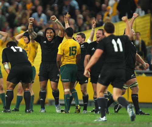 The All Blacks throw their arms up in triumph