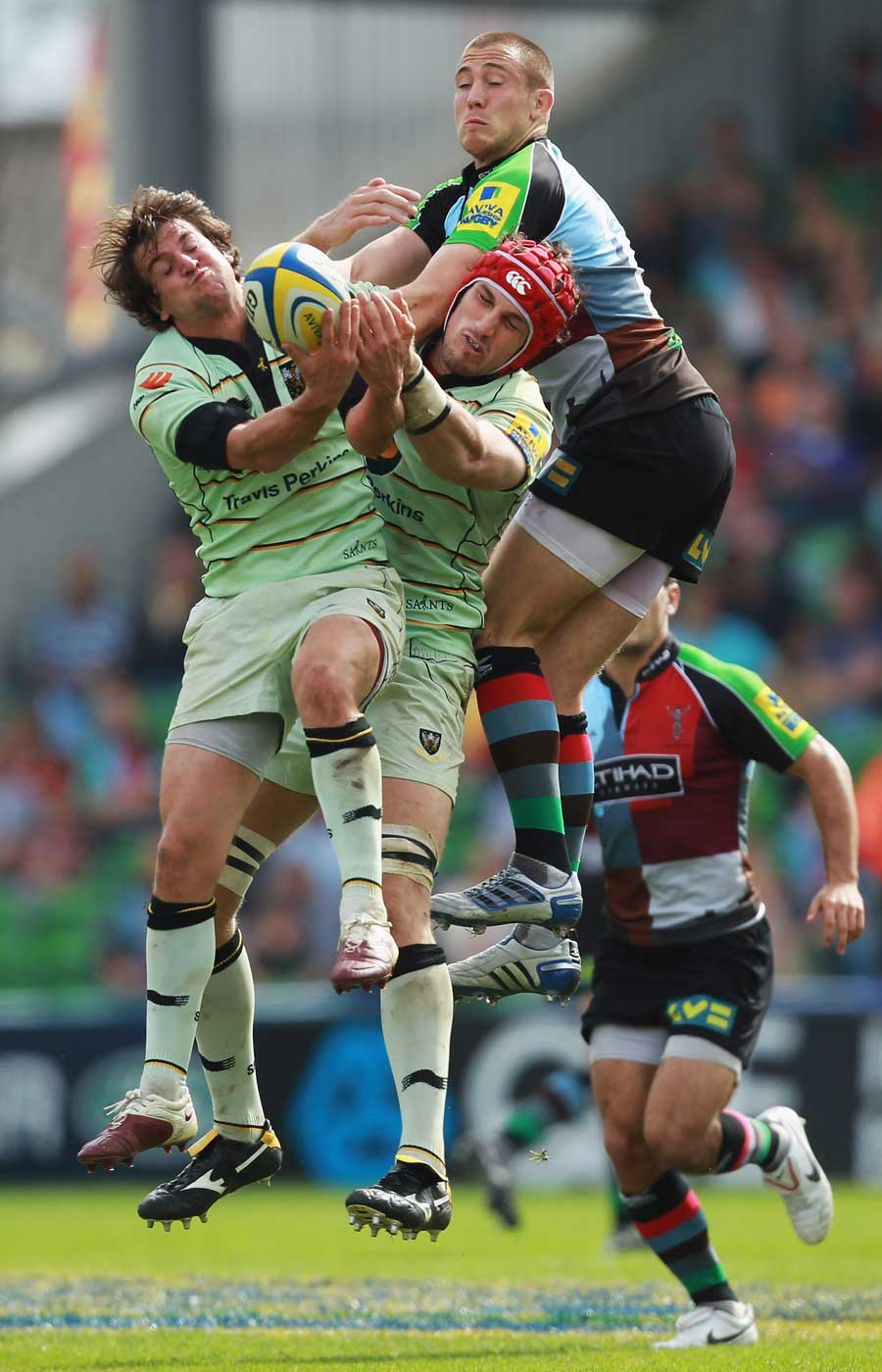 Harlequins' Mike Brown competes for a high ball with Saints' Lee Dickson and Christian Day