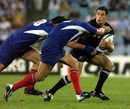 Daniel Carter of New Zealand tackled by France's Fabien Pelous and Christian Labit.
