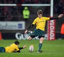 Australia's Luke Burgess helps skipper Berrick Barnes kick for goal