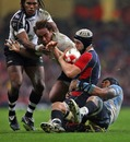 Wales' Ryan Jones is hauled down by the Fiji defence