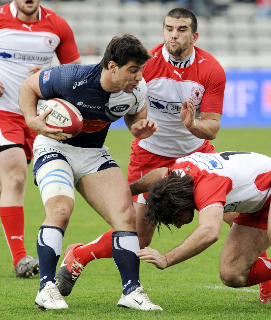 Agen centre Miguel Avramovic tries to evade Biarritz centre Marcelo Bosch