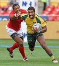 Seilame Tukuafu of Tonga tries to lay his hands on Daniel Yakapo of Australia