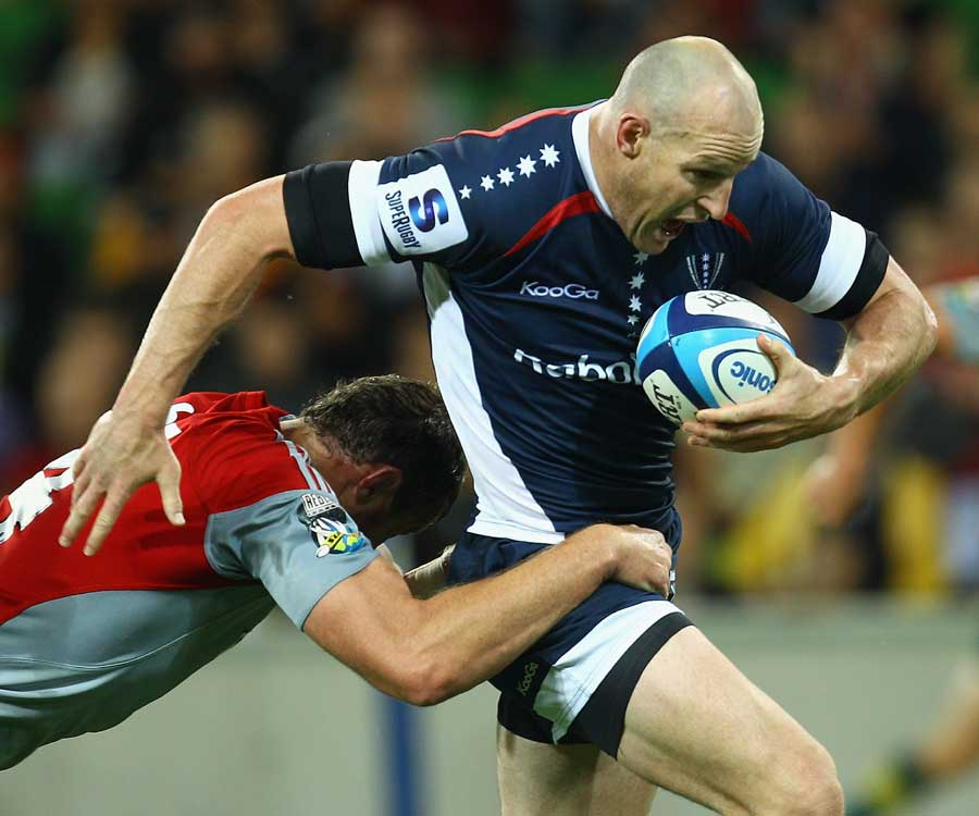 Melbourne Rebels' Stirling Mortlock tries to break the tackle against the Crusaders