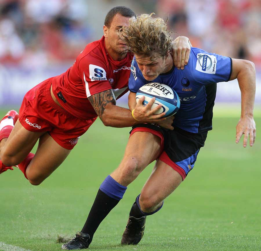 Western Force's Nick Cummins is tackled by the Reds' Quade Cooper