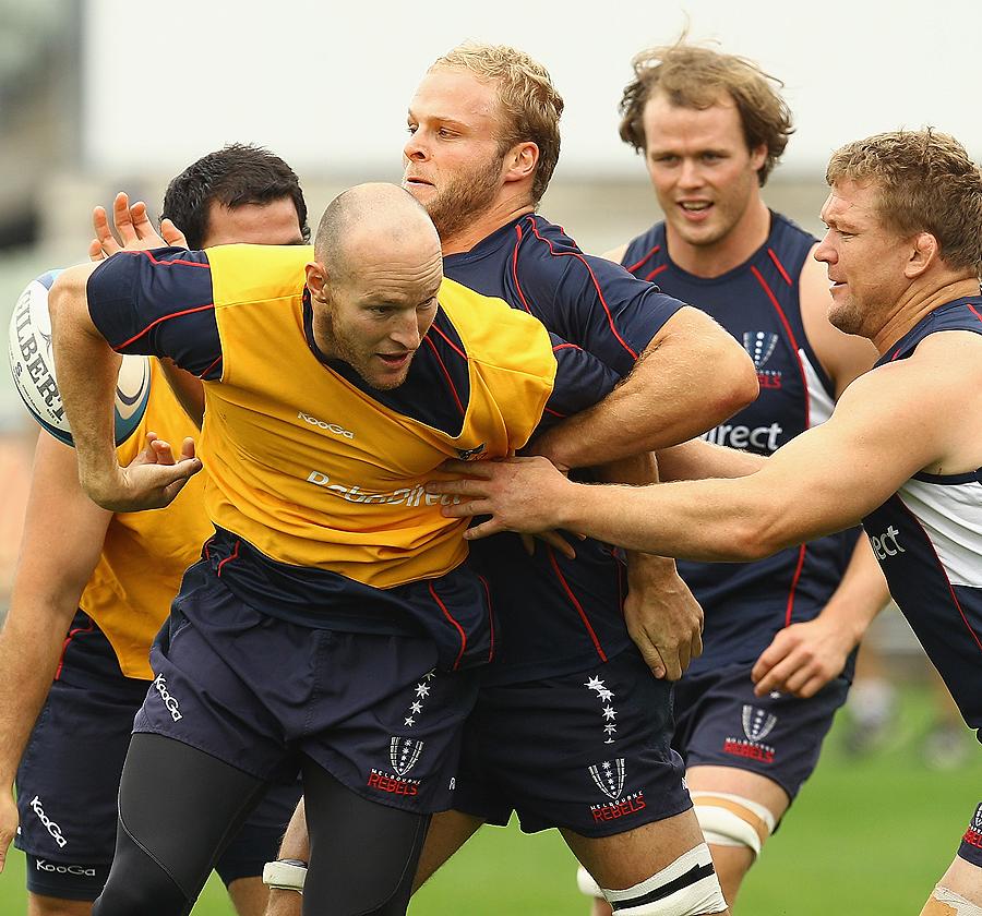 Stirling Mortlock is held back by Melbourne Rebels team-mates at training