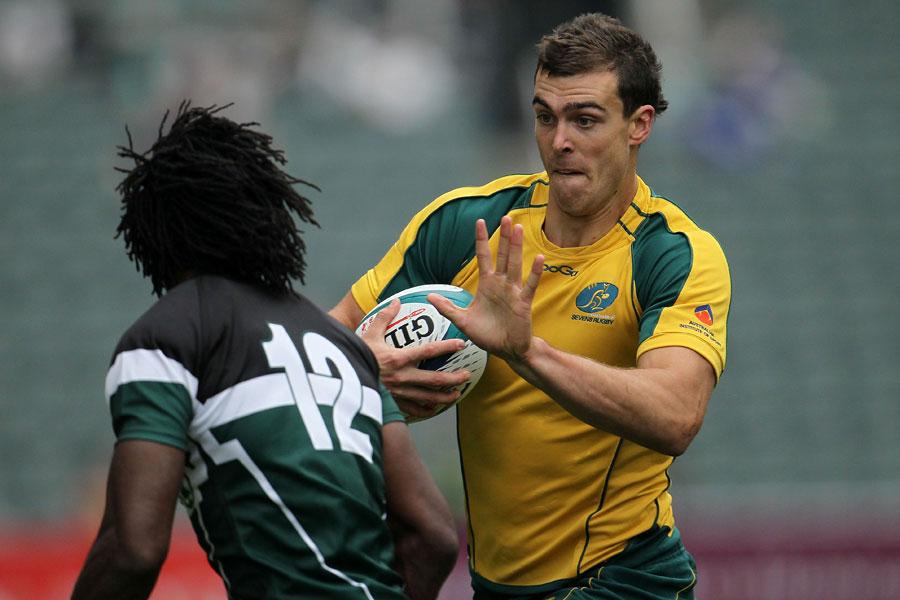 Australia's John Grant fends off a Zimbabwean defender