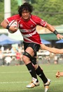 Takashi Kikutani of Japan runs with the ball