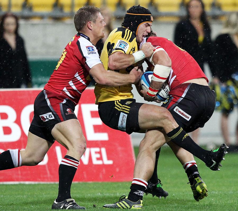 The Lions' Jaco Taute and Deon van Rensbur team up to tackle the Hurricanes' Jayden Hayward
