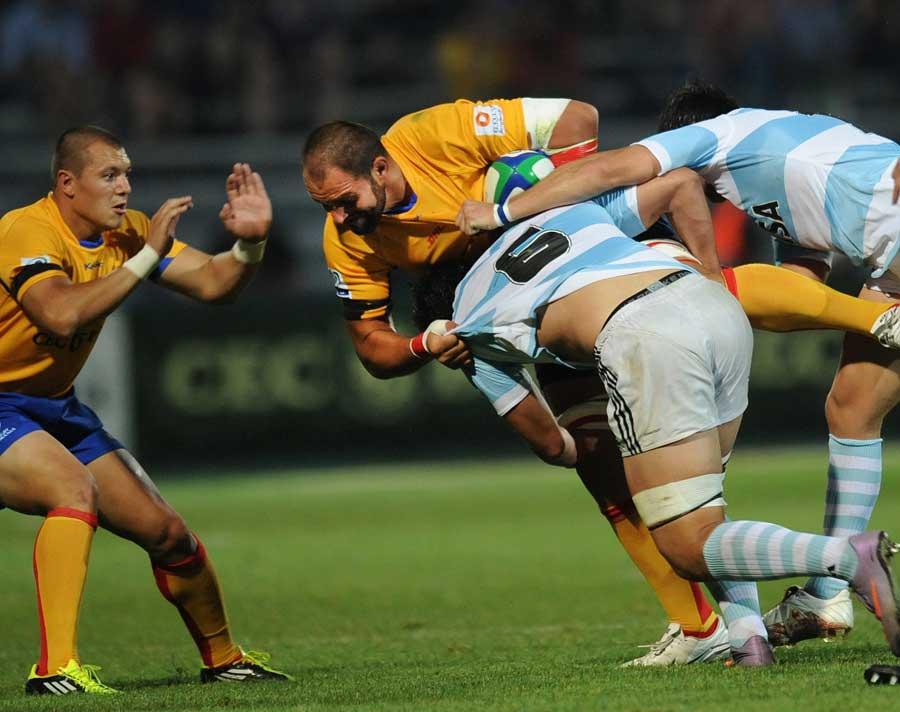 Argentina Jaguars' Tomas de la Vega tussles with Romania's Iulian Dumitras