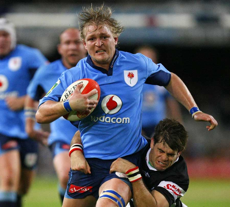 The Blue Bulls' Dewald Potgieter is tackled by the Sharks' Louis Ludik