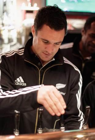 New Zealand's Dan Carter pulls a pint