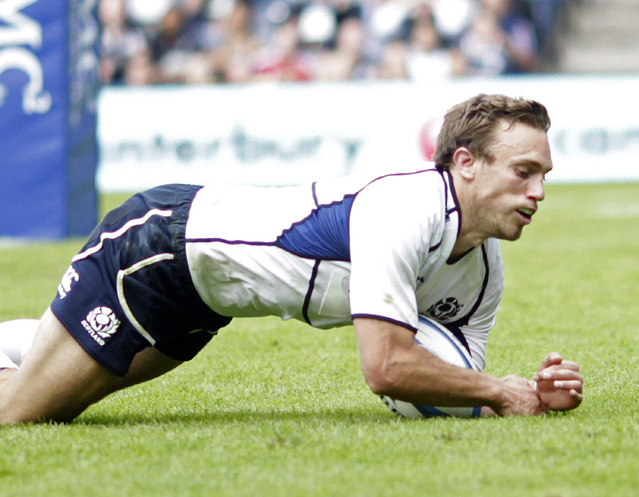 Scotland scrum-half Mike Blair dives on the ball to score following a charge down