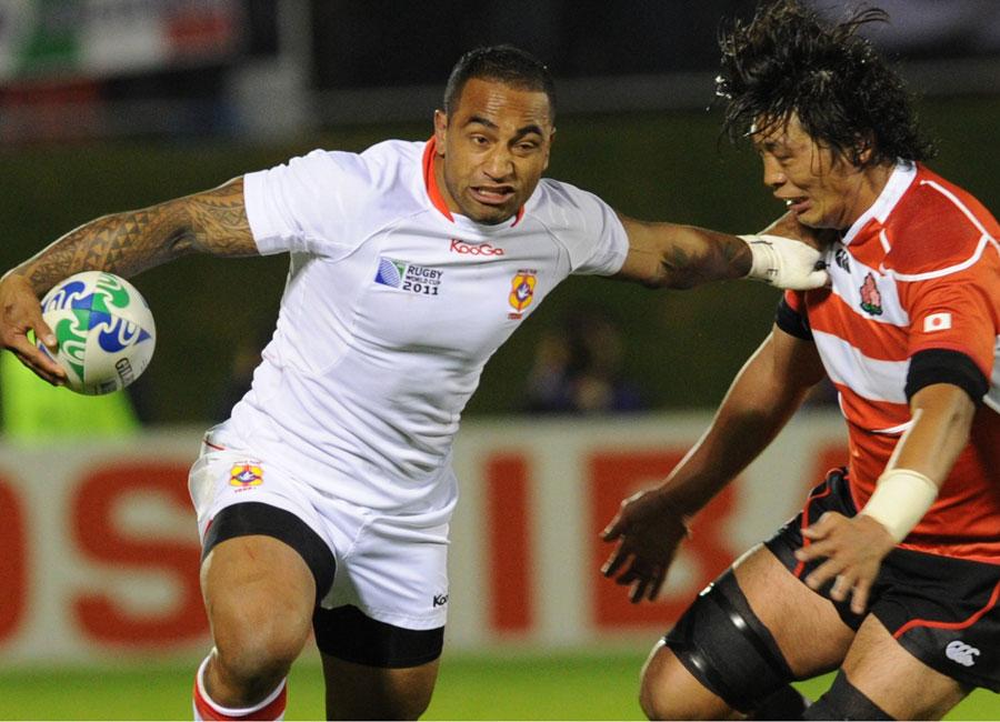Tonga winger Fetu'umoana Vainikolo fends off  pushes Japan's Toshizumi Kitagawa