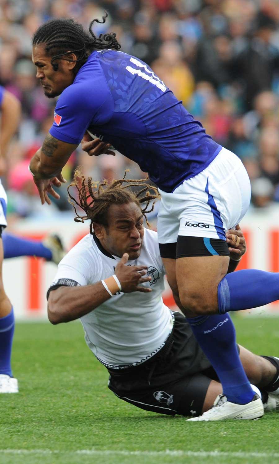 Samoa's Alesana Tuilagi is tackled by Gaby Lovobalavu