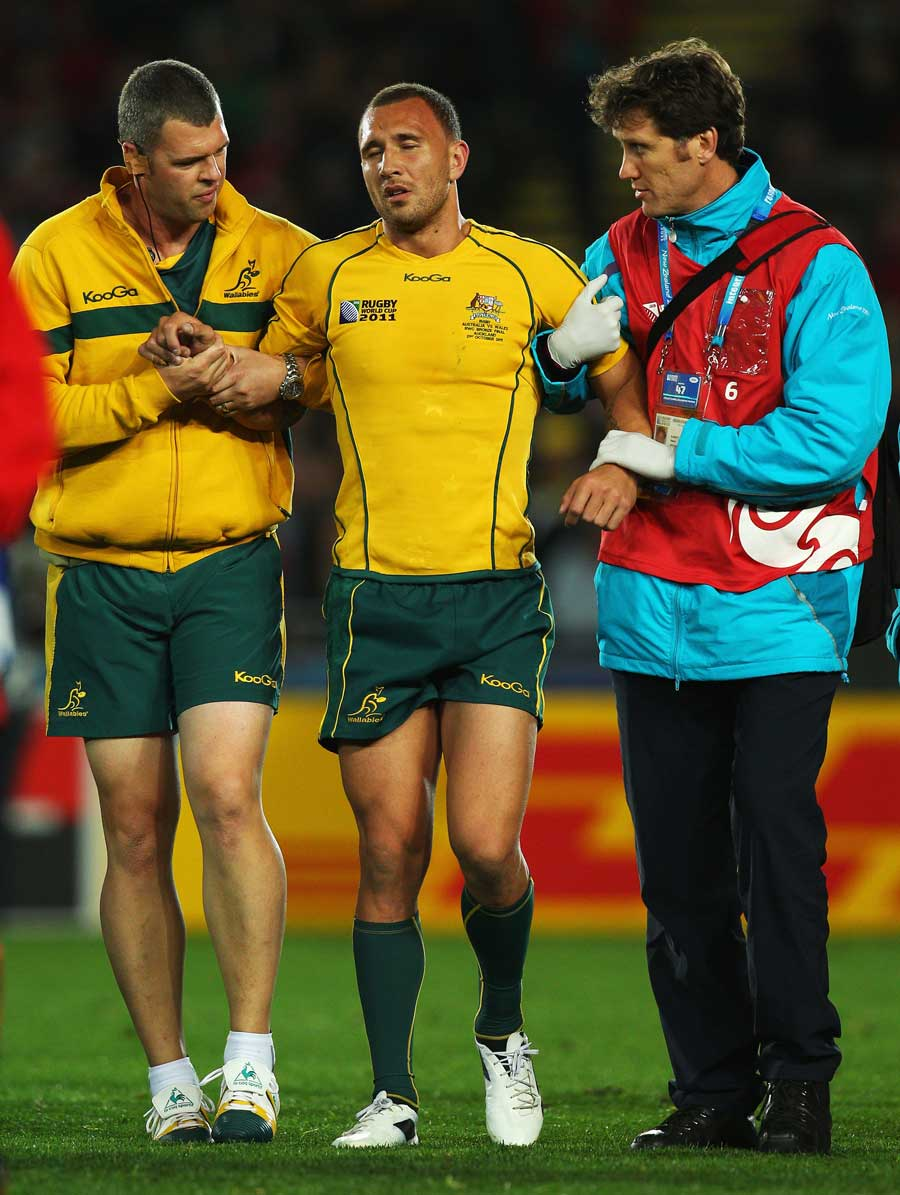Australia's Quade Cooper is helped from the field