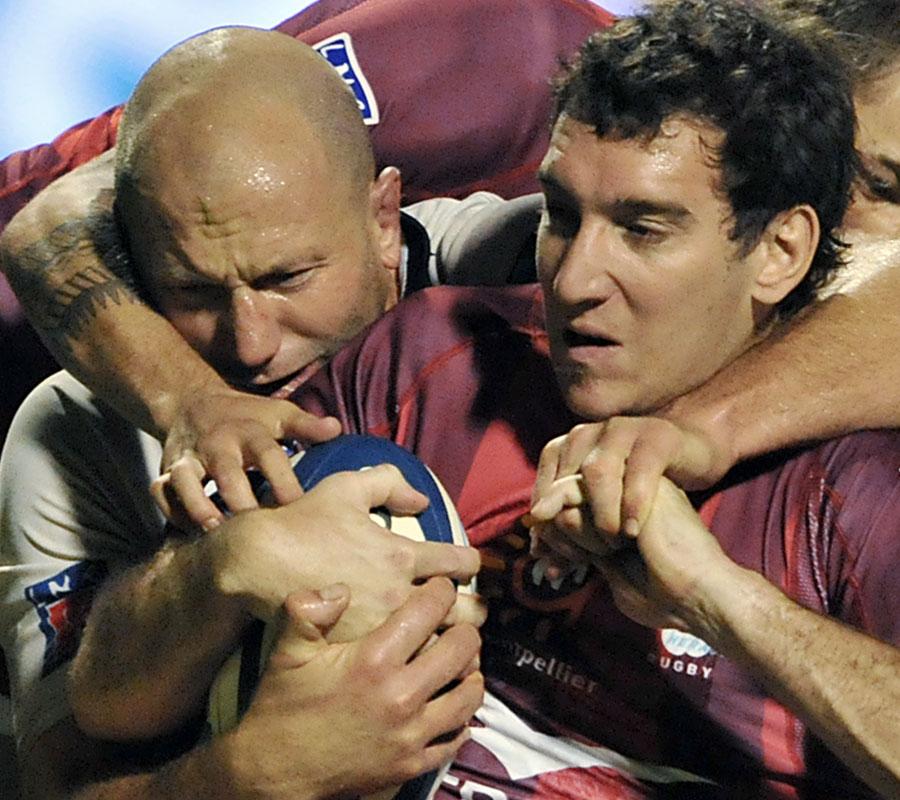 Agen's Adri Badenhorst is tackled by Montpellier' Santiago Fernandez