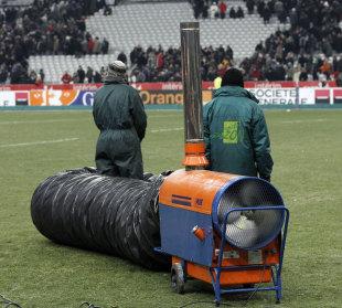 Ground staff prepare the Stade de France pitch