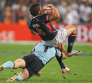 Hong Kong's Richard Smith is hit hard by the Uruguay defence