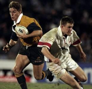 Australia's Tim Horan runs through Matt Perry