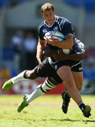 Scotland's Mark Robertson powers through a Fijian tackle