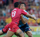 NSW Waratah's Israel Folau is wrapped up by the Queensland Reds' defence