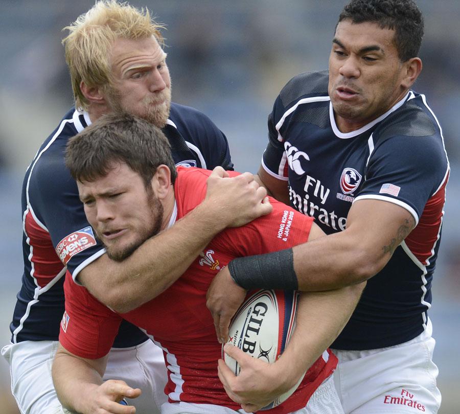 Wales' Adam Thomas is tackled by USA's Matt Hawkins and Folau Niua