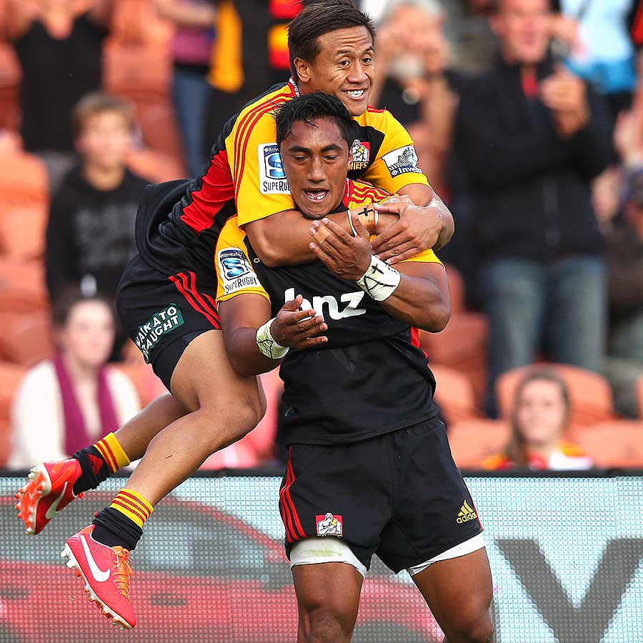 The Chiefs' Bundee Aki (front) celebrates his try against the Reds with Tim Nanai-Williams