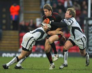 Saracens' Chris Wyles is tackled by Bristol's Ed Barnes (R) and Robert Sidoli