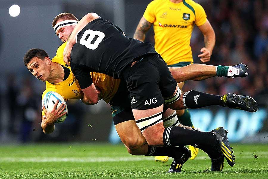 New Zealand's Kieran Read and Sam Cane tackle Matt Toomua