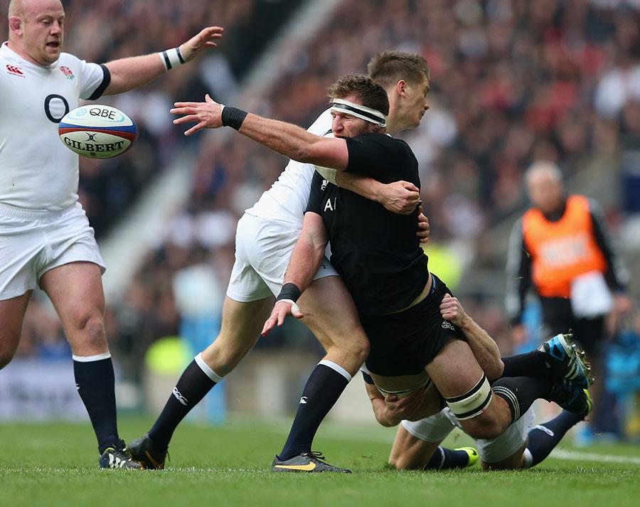 Kieran Read offloads under heavy pressure from England's Owen Farrell