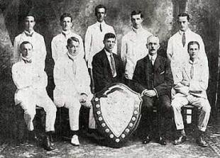 "The first committee of the Fiji Rugby Football Union, photographed on the occasion of the presentation of the Escott Shield in 1913. Seated directly behind the shield is PJ "" Paddy"" Sheehan, beside him in the other dark suit is then Governor, Sir Ernest Bickham Sweet-Escott"