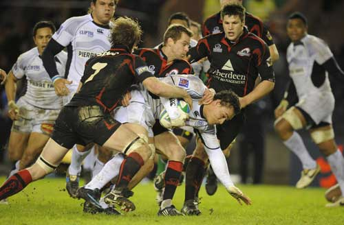 Castres' Christopher Masoe is tackled by the Edinburgh defence