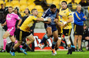 Charles Piutau of the Blues is smothered by the Hurricanes' defence
