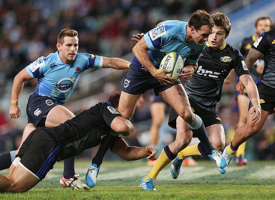 The Waratahs' Matthew Carraro runs through a tackle