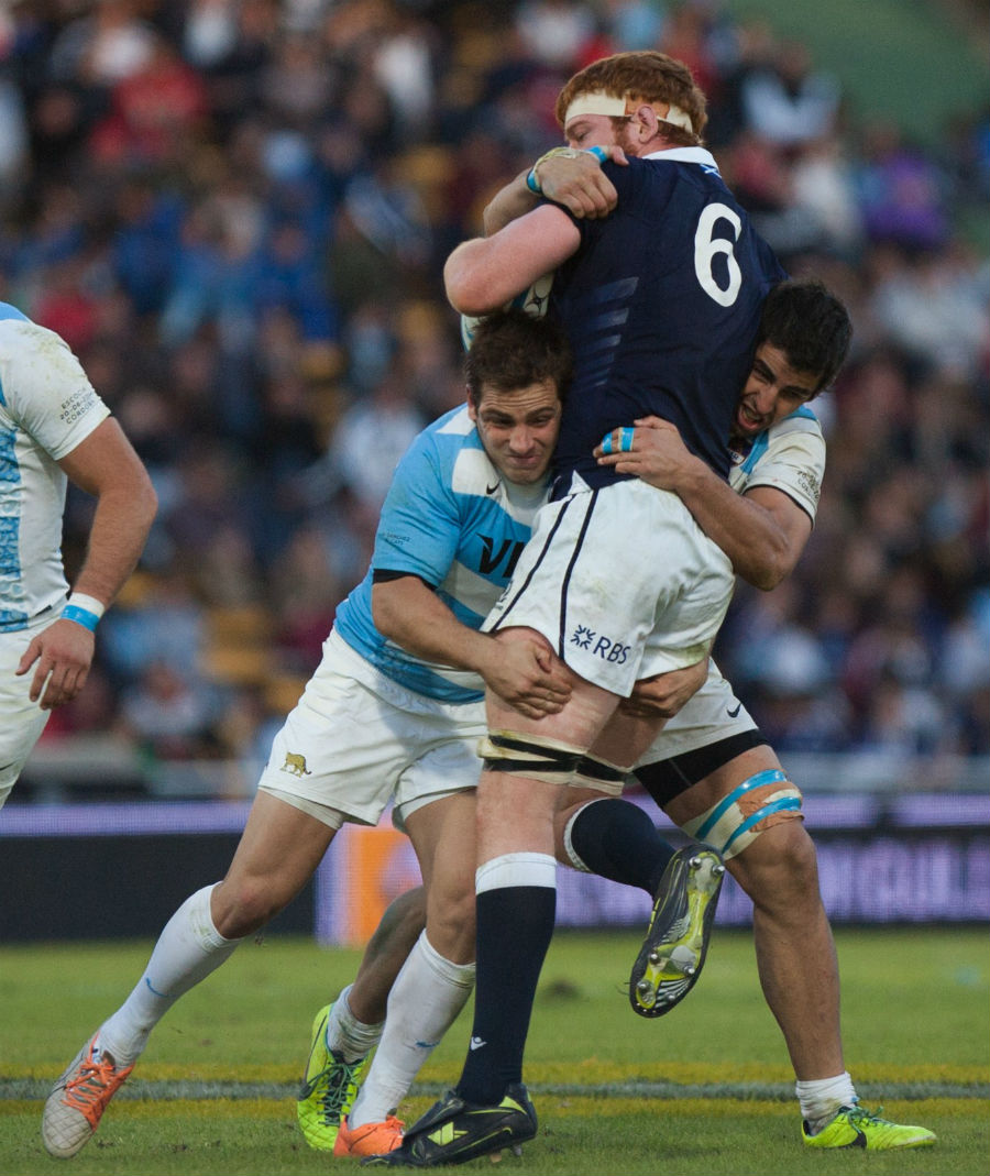 Rob Harley is tackled by Argentina's fly-half Nicolas Sanchez and Tomas de la Vega