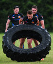 Henry Slade flips a tyre in the rain during an Exeter Chiefs training session