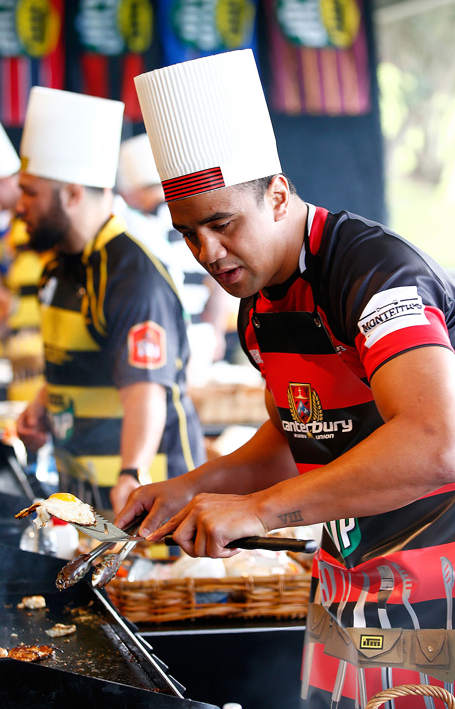 Canterbury's Nasi Manu cooks during a hamburger competition at the ITM Cup season launch