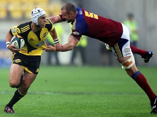 The Hurricanes' Daniel Kirkpatrick is tackled by the Highlanders' Hayden Triggs