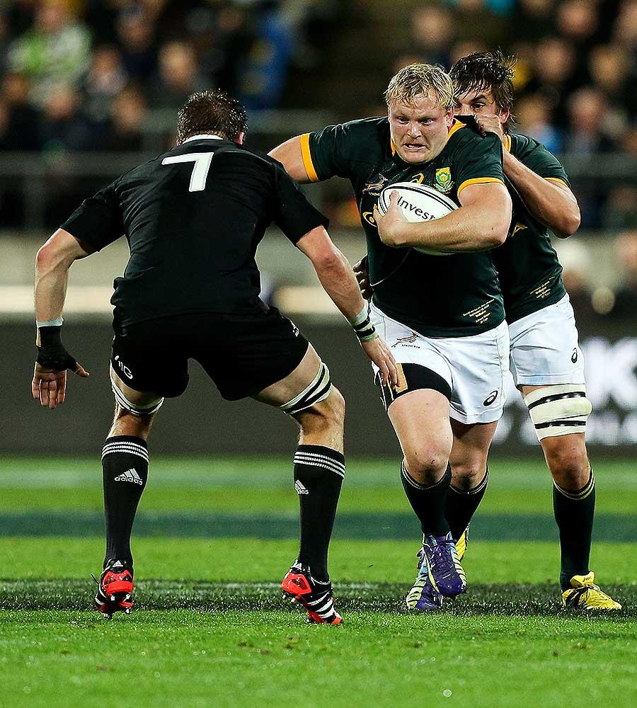 South Africa's Adriaan Strauss runs at Richie McCaw